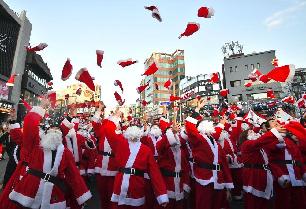 Papais Noéis sul-coreanos jogam gorros ao ar durante cerimônia de Natal, em Seul, Coreia do Sul, 24 de dezembro de 2018