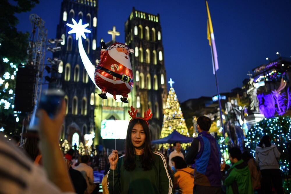 Vietnamita posa com balão de Papai Noel perto de catedral na cidade de Hanói, Vietnã, em 24 de dezembro de 2018