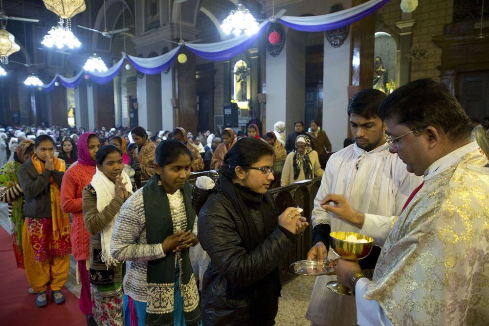 Padre distribui hóstia durante missa da meia-noite de Natal em Allahabad, Índia, 25 de dezembro de 2018
