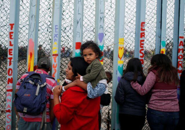 Uma mulher é fotografada com o filho reunião em apoio à caravana de migrantes em San Diego, EUA, perto da fronteira entre os Estados Unidos e o México, em Tijuana.