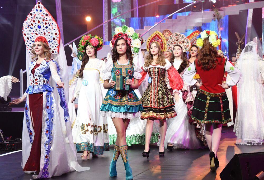 Participantes do concurso internacional Enviadas da Beleza 2018 mostrando trajes nacionais em desfile