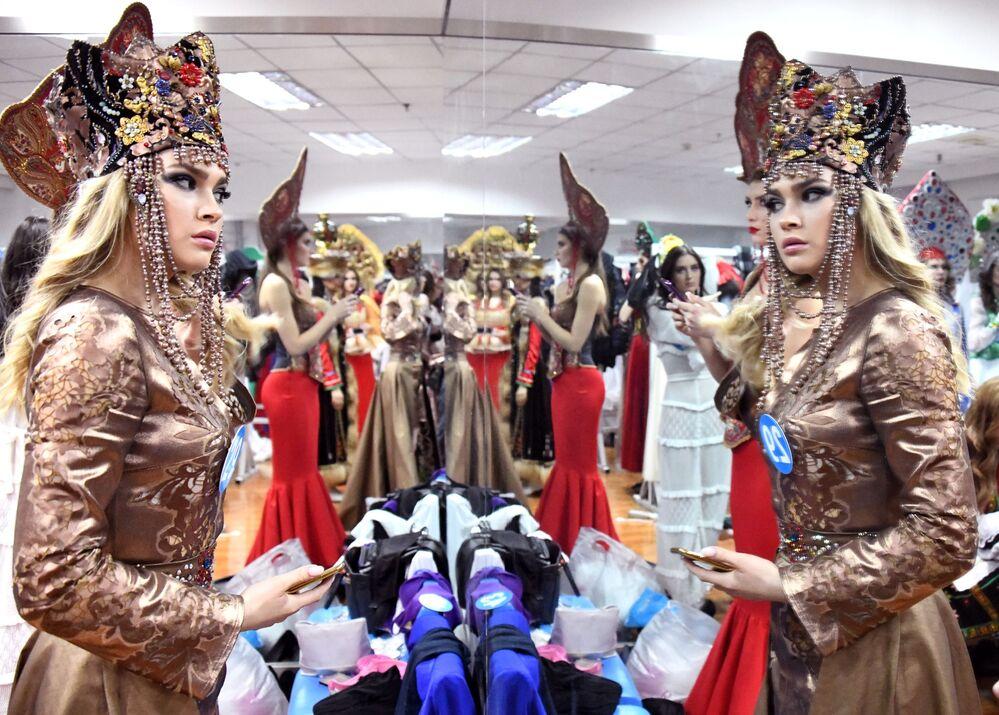Participante do concurso internacional Enviadas da Beleza 2018 se prepara para aparecer na passarela usando traje nacional