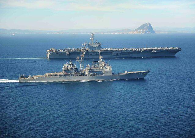 USS Vicksburg escoltando o porta-aviões USS Theodore Roosevelt enquanto passam pela Pedra de Gibraltar no Mar Mediterrâneo