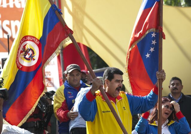 Venezuela's President Nicolas Maduro holds up a Colombian national flag, left, alongside his country's national flag, during a rally in support of closing the Colombian border, in Caracas, Venezuela, Friday, Aug. 28, 2015.