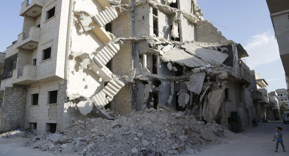 Uma garota caminha perto de um prédio danificado em Maarat Al-Nouman, ao sul de Idlib, Síria (foto de arquivo)