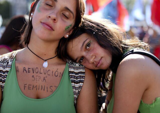 Uma mulher usa uma mensagem no peito que diz em espanhol: A revolução será  feminista.