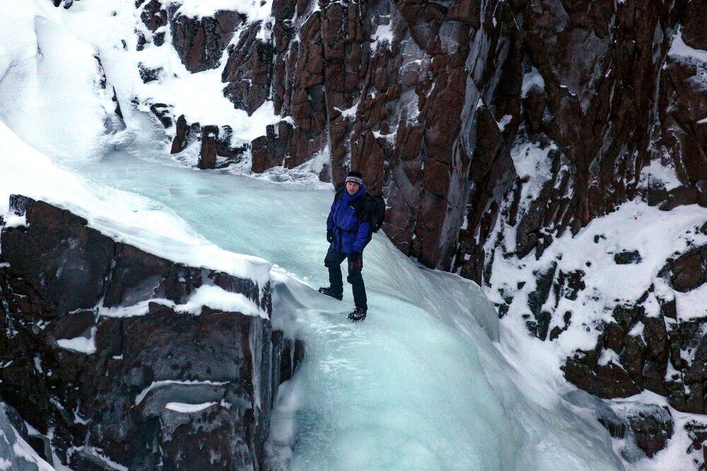 Turista escalando a cachoeira congelada, na península de Kola, na Rússia
