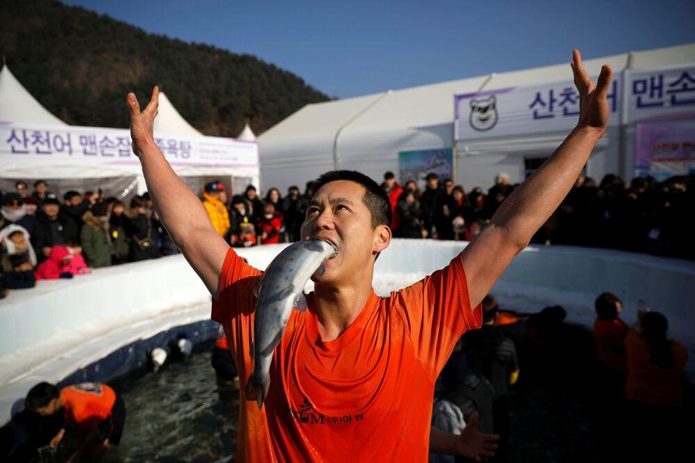 Um homem satisfeito por ter apanhado um peixe com as mãos durante um festival de truta na cidade sul-coreana de Hwacheon.