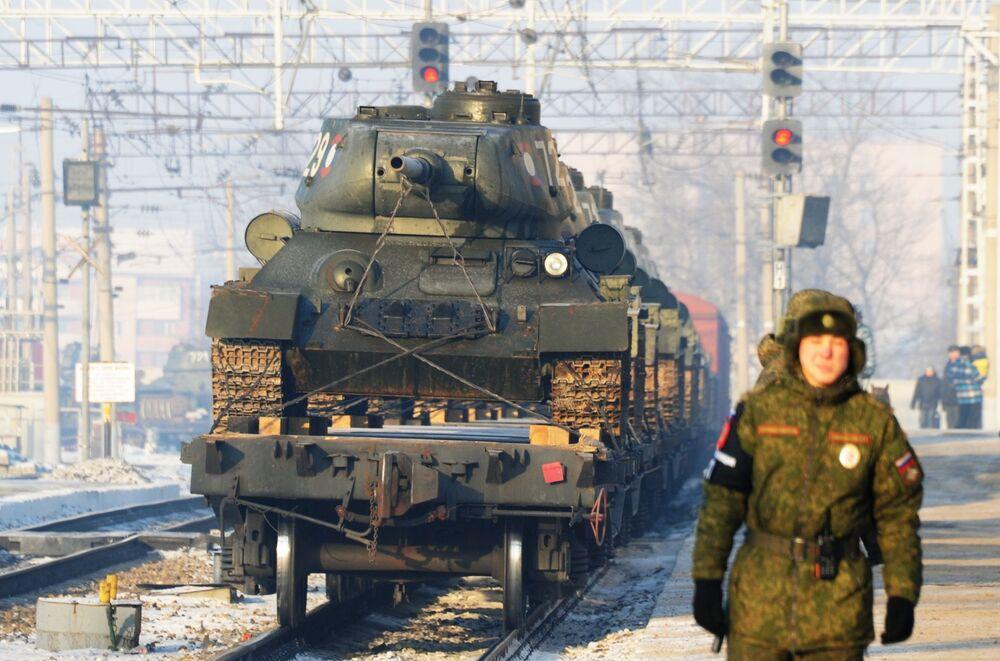 Um militar perto de tanques de produção soviética T-34 transportados do Laos para a Rússia