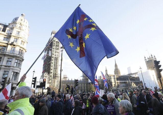 Manifestantes seguram cartazes e bandeiras na manifestação contra a Traição ao Brexit, em frente às Casas do Parlamento em Londres.