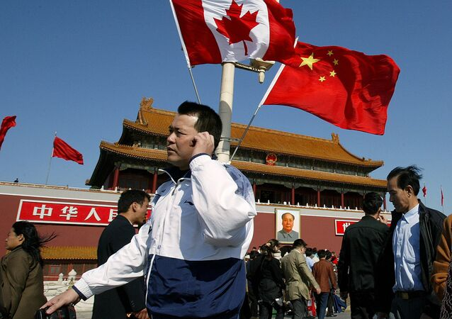 A man walks past flags of Canada and China in front of Tiananmen Gate in Beijing (File)