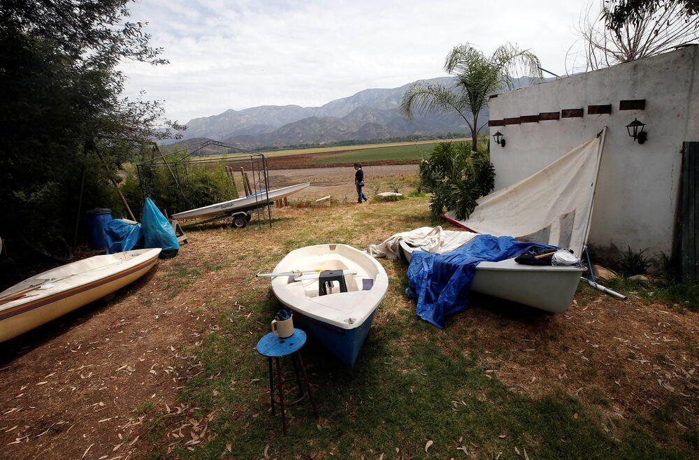 Barcos no quintal de uma casa que se encontra à beira da lagoa