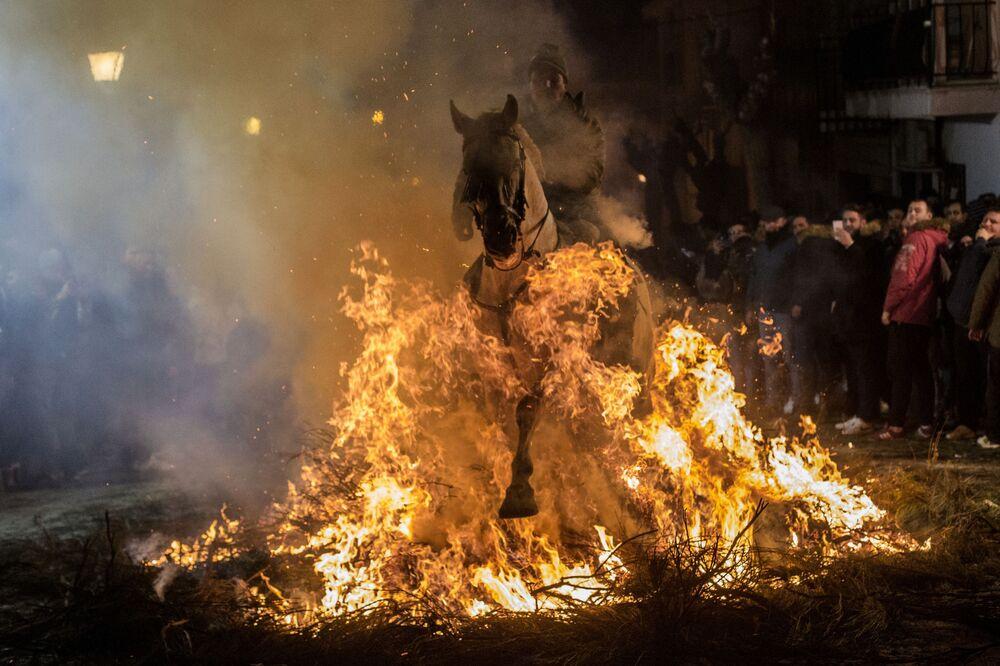 Cavaleiro passando pelo fogo durante o festival anual Las Luminarias na cidade espanhola de San Bartolomé de Pinares