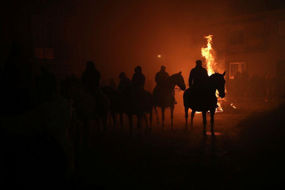 Homens montados em cavalos esperando o início das corridas durante o festival anual Las Luminarias no município espanhol de San Bartolomé de Pinares