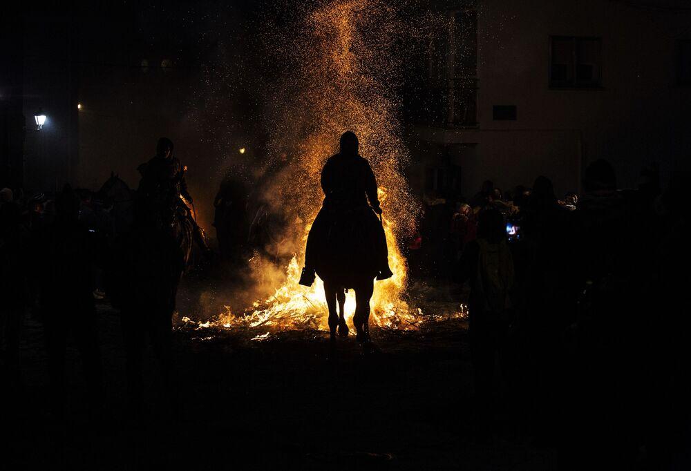 Homem montado em cavalo admira fogueira do festival anual Las Luminarias