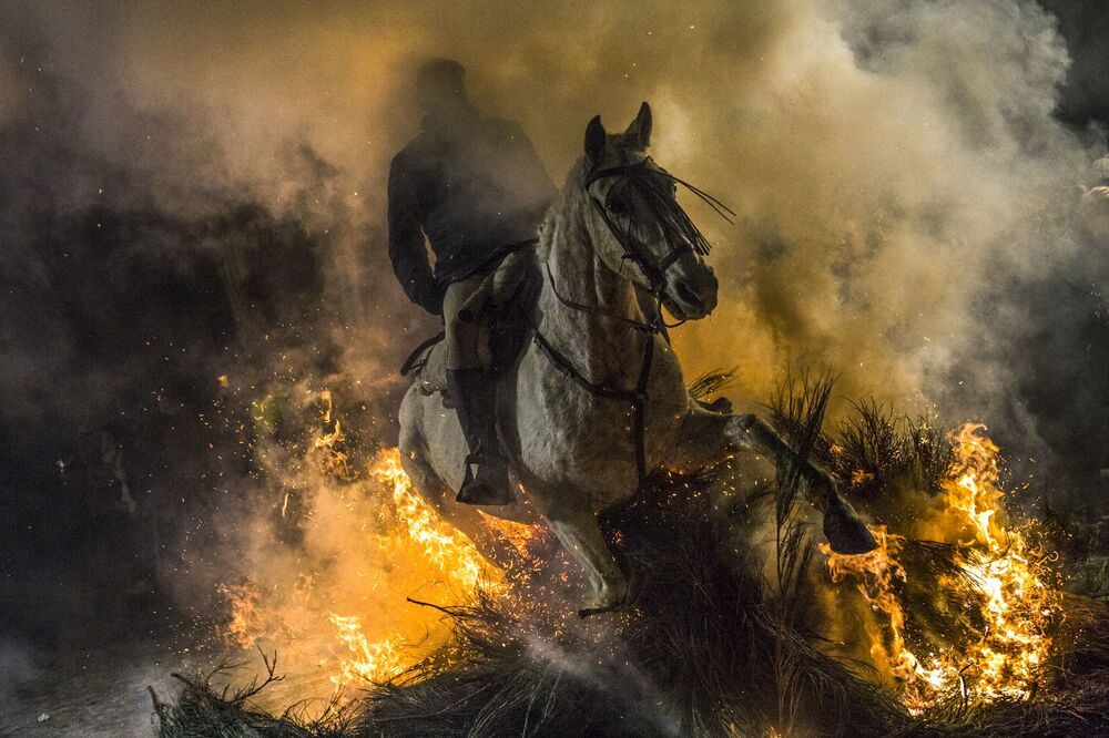Cavaleiro atravessa o fogo no festival Las Luminarias, na vila espanhola de San Bartolomé de Pinares
