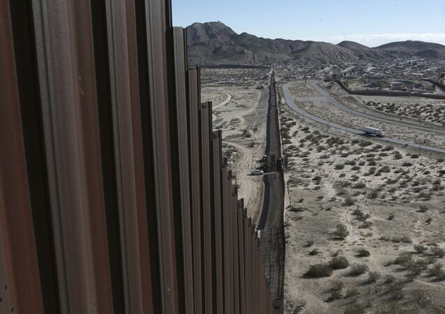 Um caminhão dirige perto da cerca na fronteira entre México-EUA. De um lado está a cidade de Anapra, México e no outro Sunland Park, Novo México.