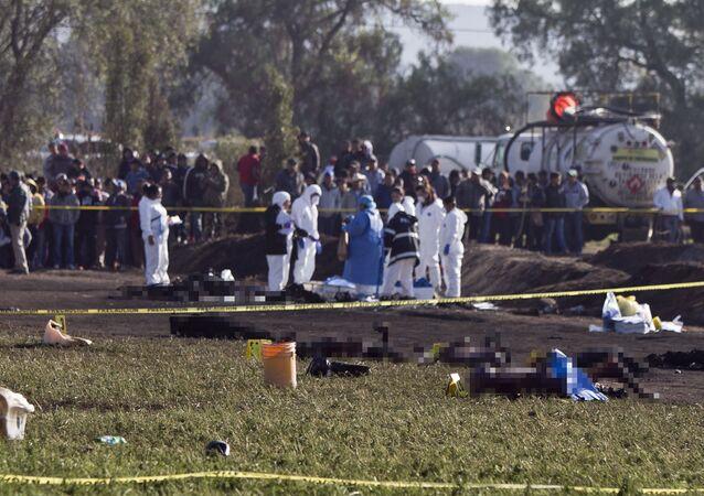 Corpos queimados são inspecionados por peritos depois da explosão do oleoduto da Pemex