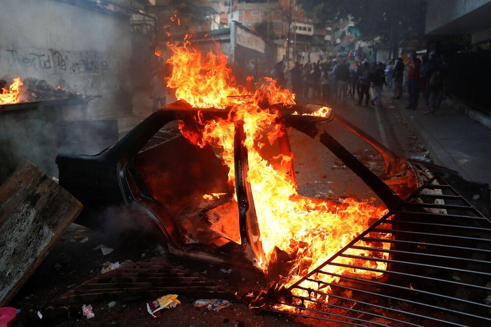 Carro em chamas durante protestos em Caracas, Venezuela