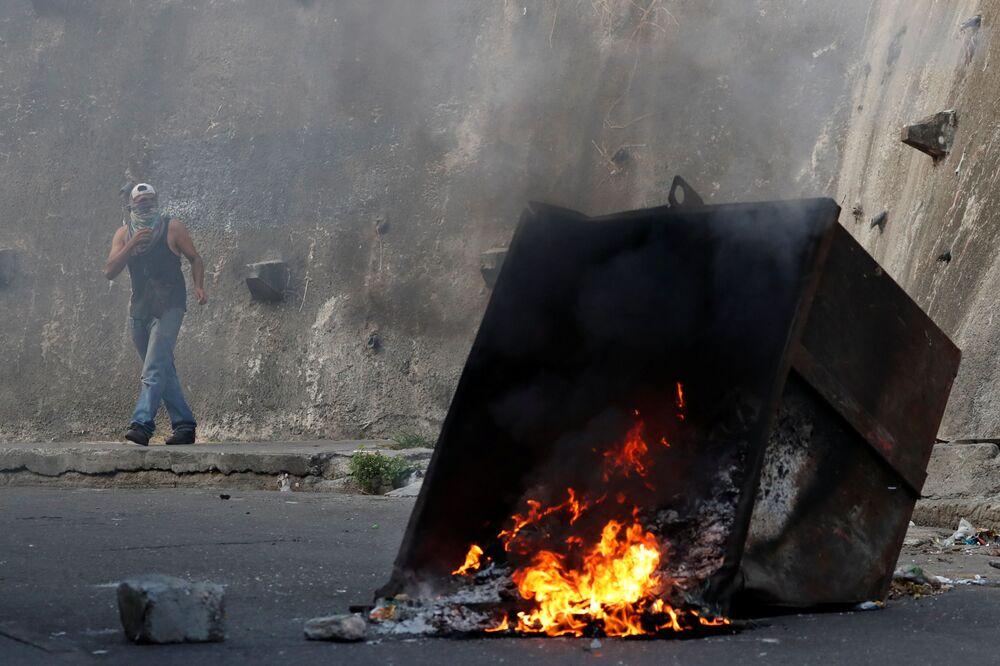 Manifestante por trás de uma barricada em chamas durante protestos em Caracas, Venezuela