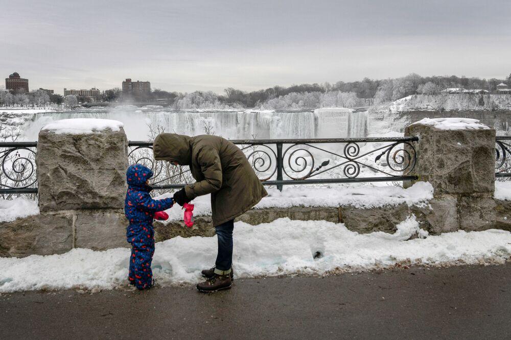 Homem com uma criança perto das cataratas do Niágara no Canadá
