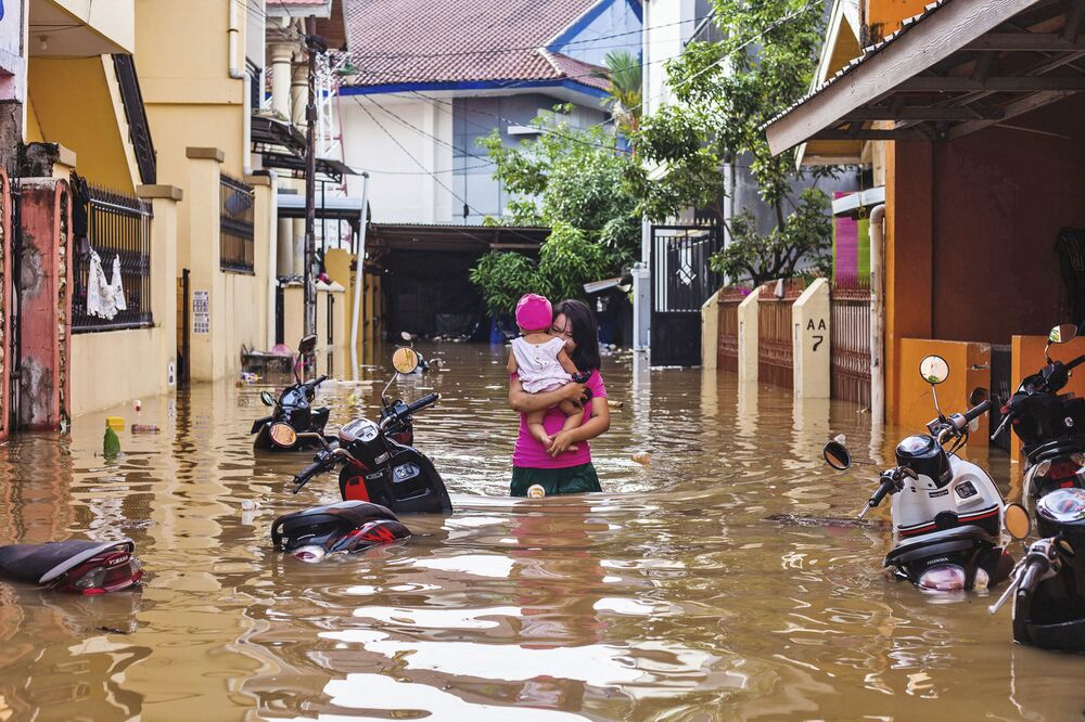 Mulher carrega criança em uma rua inundada na cidade indonésia de Makasar, 23 de janeiro de 2019