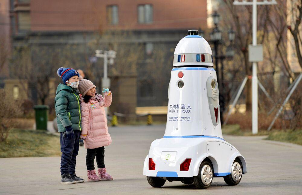 Crianças observam robô de segurança patrulhando complexo residencial na cidade de Hohhot, na China, 18 de janeiro de 2019