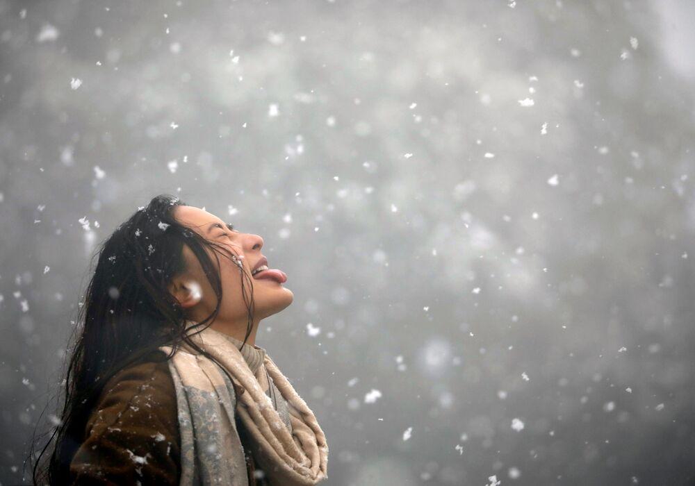 Jovem pega flocos de neve com a boca durante queda de neve em Kathmandu, no Nepal, 23 de janeiro de 2019