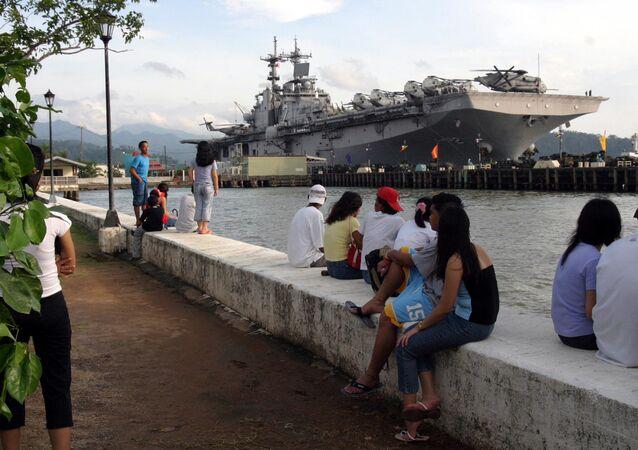 Pessoas perto do navio anfíbio norte-americano USS Essex, Subic Bay, Filipinas