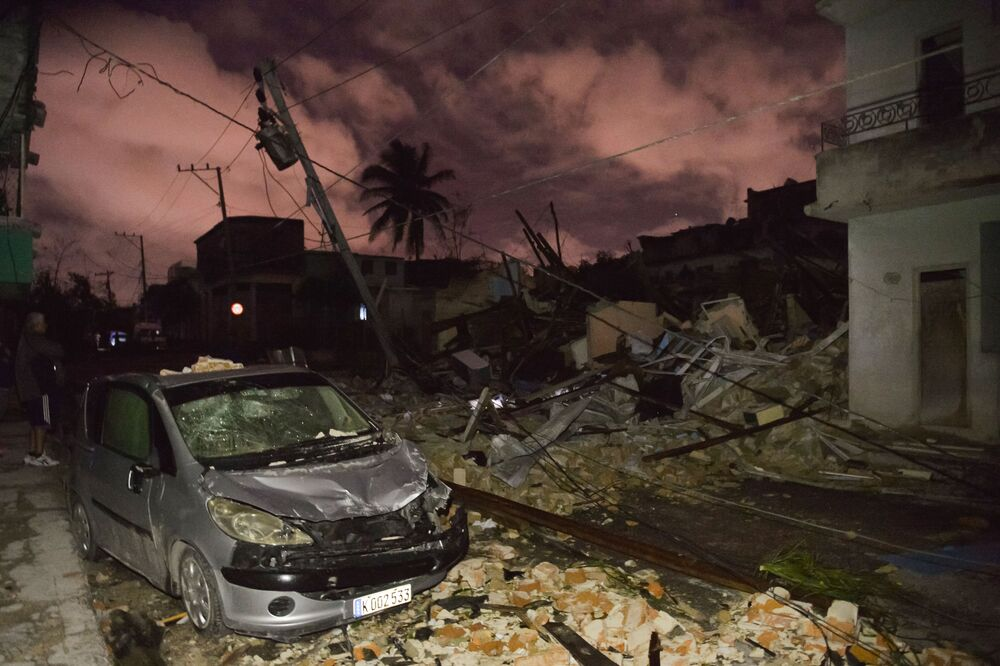 Carro danificado no meio de prédios reduzidos a ruínas depois do tornado na capital de Cuba