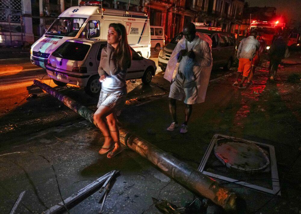 Residentes cubanos passam pelas ruas de Havana destruída em resultado do tornado