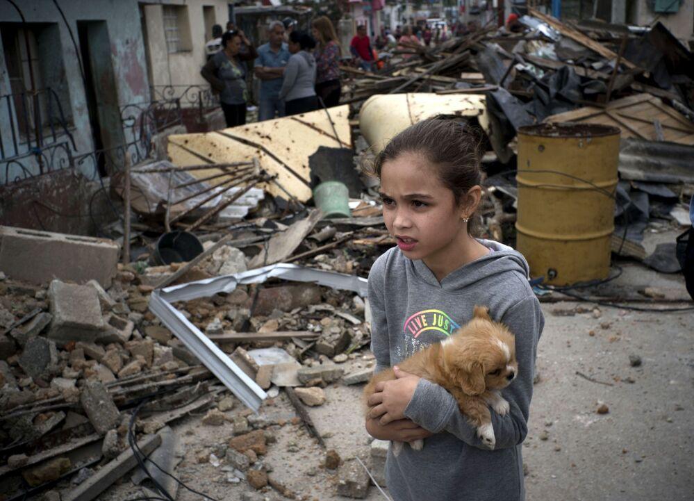 Menina com cachorro nos destroços em Havana