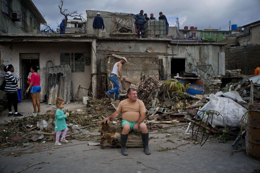 Cubano descansa da eliminação das consequências do tornado sentado no tronco de uma árvore derrubada