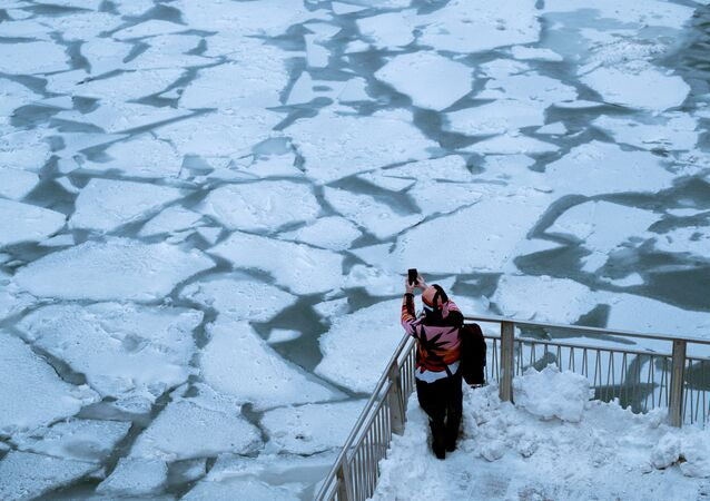 Garota tira foto do rio Chicago tomado pelo vórtice polar que atingiu a maioria dos estados norte-americanos ocidentais e centrais