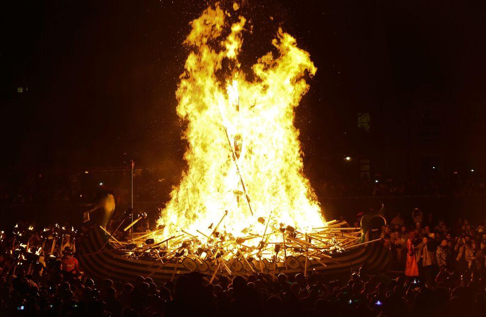 Membros do Esquadrão Jarl, usando roupas de vikings, colocam fogo no barco durante o festival escocês Up Helly Aa, 29 de janeiro de 2019