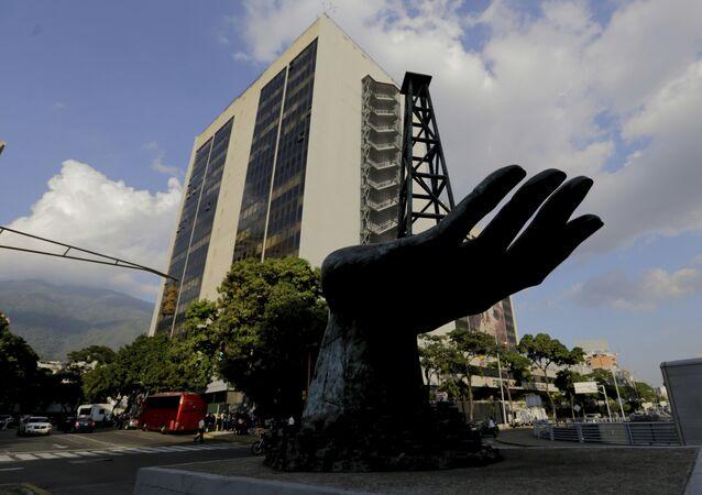 Escultura de uma mão segurando uma bomba de óleo atrás da sede da empresa venezuelana PDVSA em Caracas