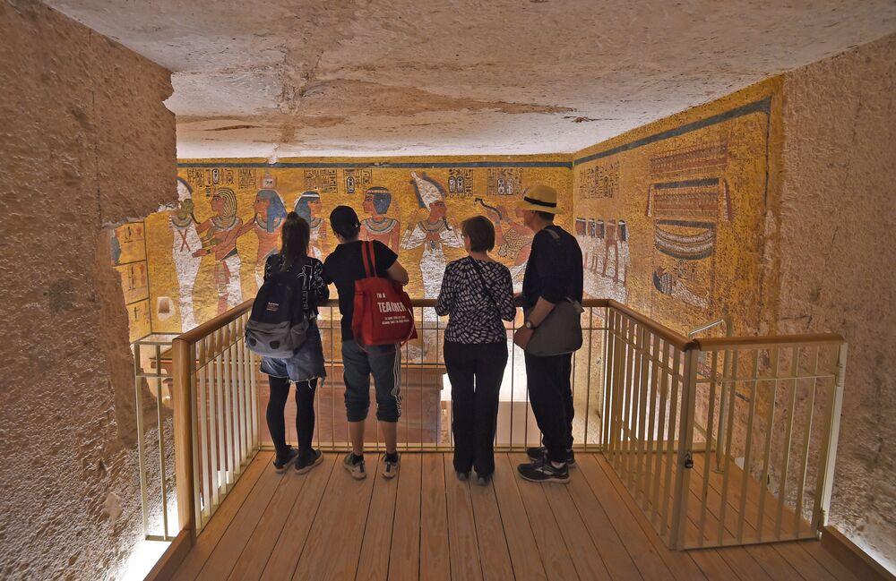 Visitantes observam as antigas pinturas egípcias exibidas na tumba restaurada do faraó