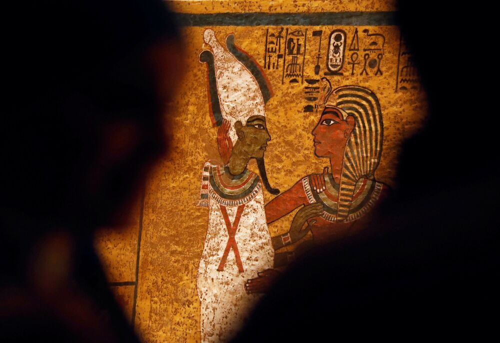 Turistas admiram as pinturas egípcias que decoram as paredes da tumba de Tutancâmon, faraó do Antigo Egito