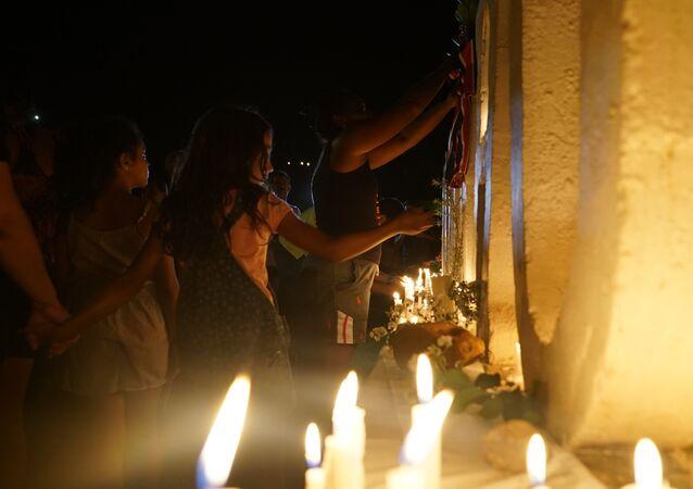 Uma criança é vista acendendo uma vela no letreiro de Brumadinho, local que se converteu em memorial em homenagem aos mortos pelo rompimento de barragem da Vale.