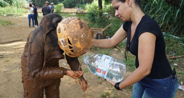 Voluntários auxiliam oficial do Corpo de Bombeiros durante trabalhos de busca por corpos em Brumadinho, Minas Gerais.