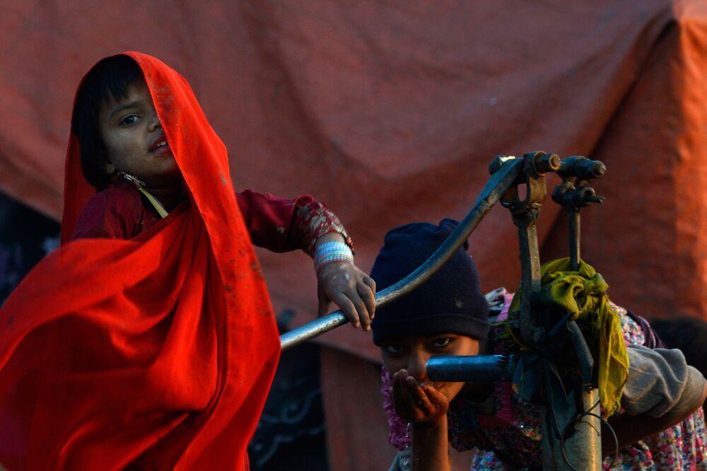 Criança cigana bebe água em bomba de mão no Paquistão
