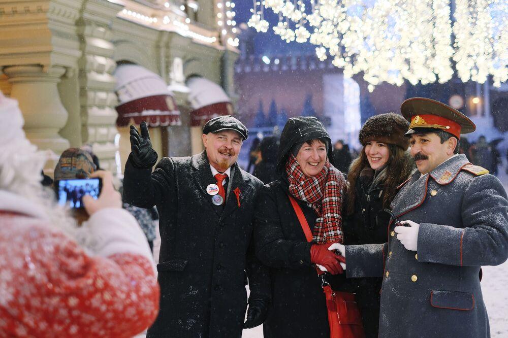 Turistas em Moscou tiram foto com homens vestidos de Vladimir Lenin e Josef Stalin