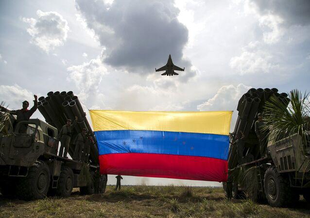 Um avião de combate Sukhoi Su-30MKV da Força Aérea Venezuelana sobrevoa uma bandeira venezuelana.