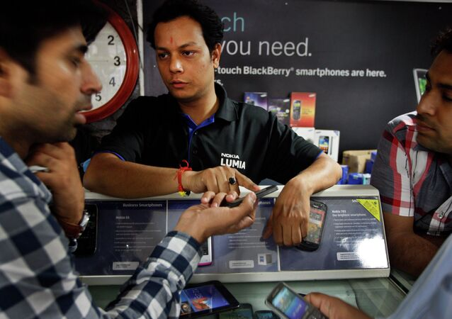 An Indian shopkeeper, center, tries to sell a Nokia mobile phone to a customer, left, in New Delhi, India