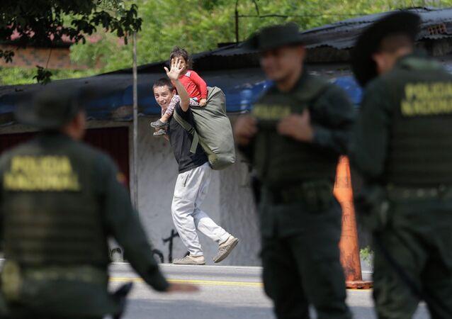 Imigrante da Venezuela acena a policiais enquanto entra na Colômbia.