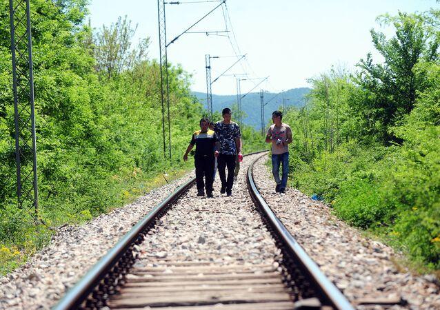 Refugiados seguem as trilhas de uma estrada de ferro perto da fronteira entre a Grécia e a Macedônia