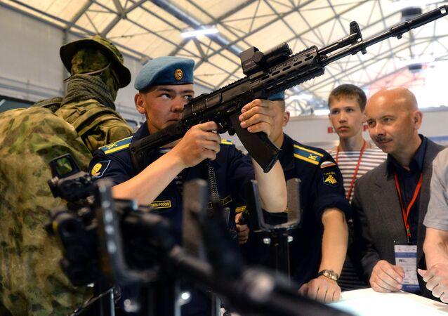 Um cadete examina o novo fuzil de assalto russo AK-12 (Consórcio Kalashnikov) durante a exposição militar internacional Army 2015 em Kubinka, Rússia.
