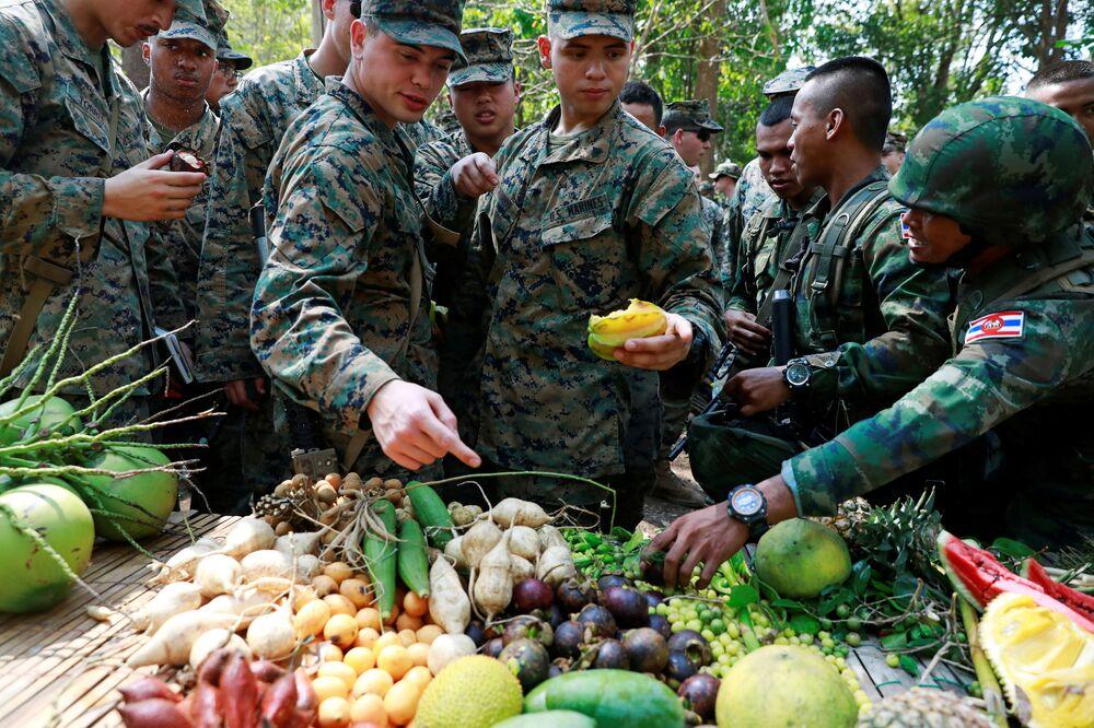 Fuzileiros navais tailandeses e norte-americanos comem frutas nas manobras Cobra Gold na Tailândia