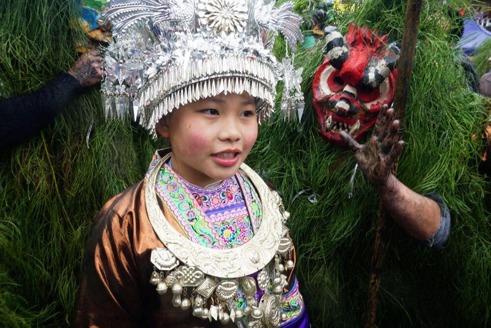 Menina de etnia Miao usa vestido tradicional durante festival em Liuzhou, na China, 13 de fevereiro de 2019