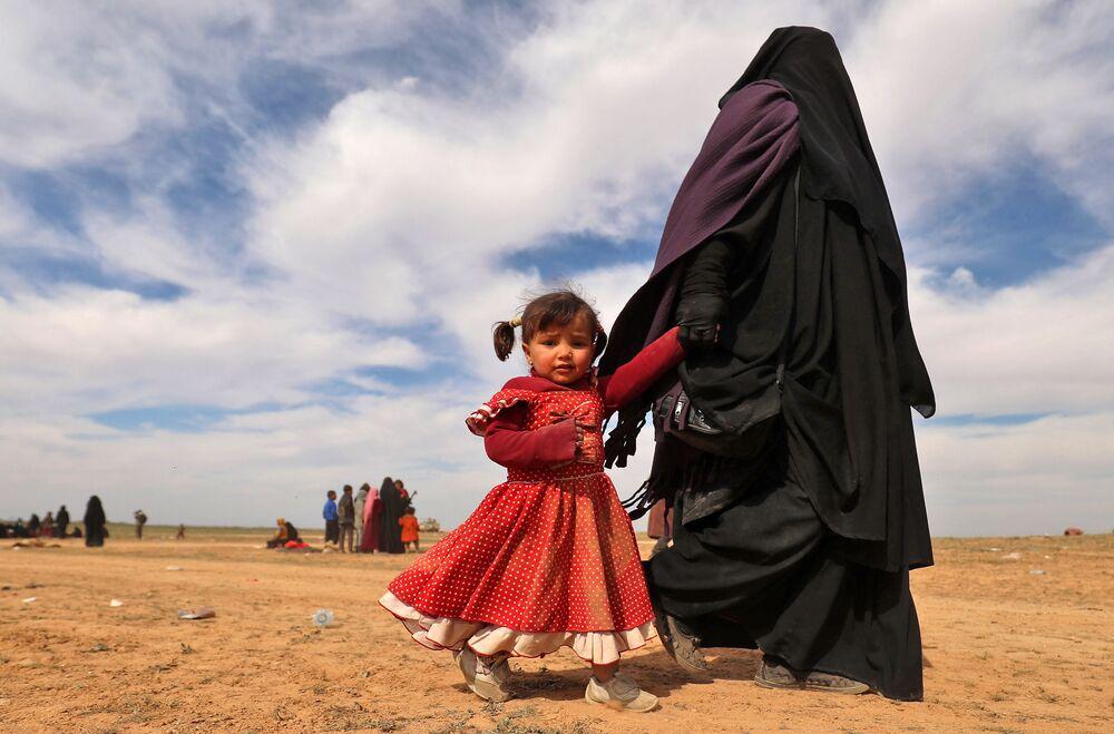 Mulher totalmente coberta caminha com filha enquanto civis, que fugiram do grupo do Estado Islâmico, reúnem-se em campo, em 13 de fevereiro de 2019